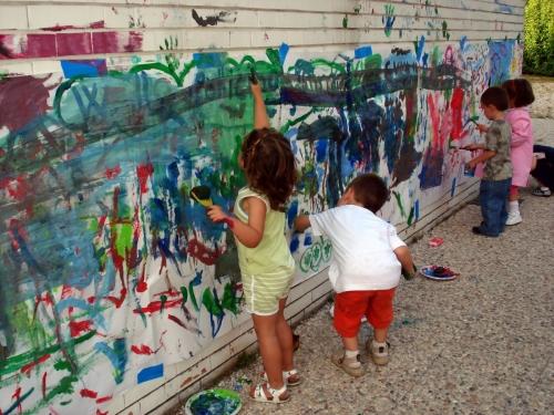 Jeunes enfants peignant ensemble une grande fresque
