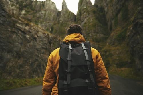Marcheur avec un sac dos se dirigeant vers une falaise