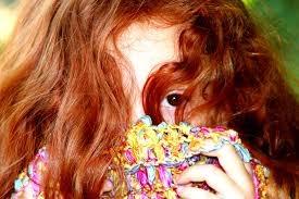 Jeune fille caché derrière son écharpe et dans ses cheveux