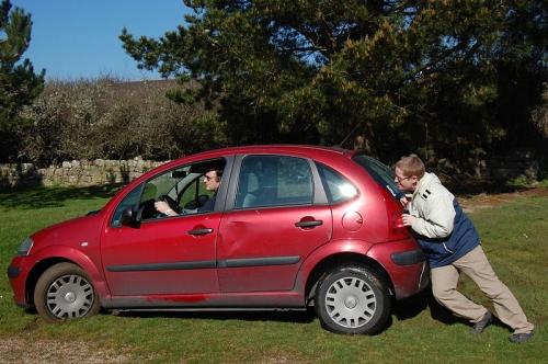 Une personne pousse une voiture embourbée